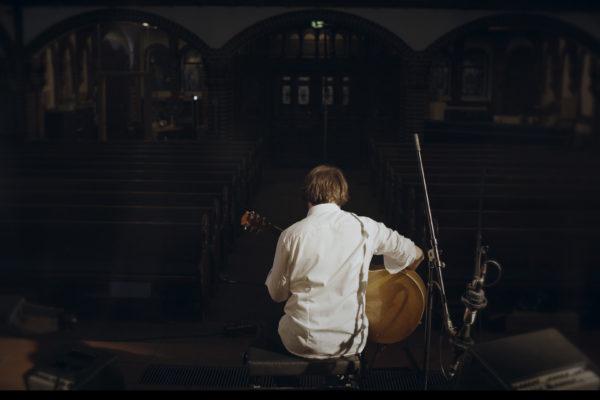 Hub Hildenbrand mit Gitarre in Kirche. Teil eines Livevideos