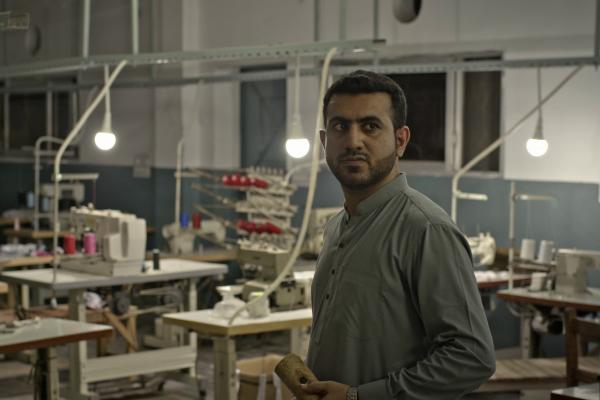 Mann schaut grimmig in pakistanischer Fabrik, Standbild aus Imagefilm für NRO / NGO